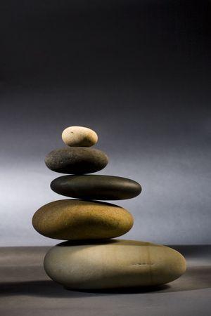 five stones in zen balance over dark background