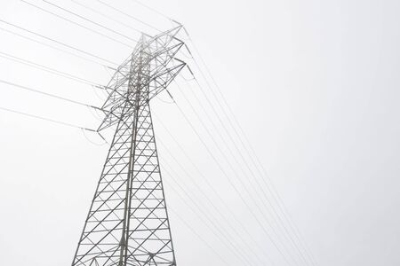 conduction: electrical tower of high voltage between light fog. Black and white Stock Photo