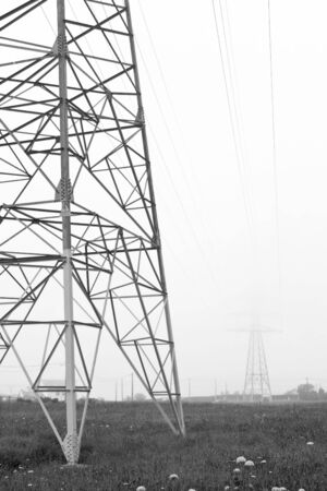conduction: electrical towers of high voltage between light fog. Black and white