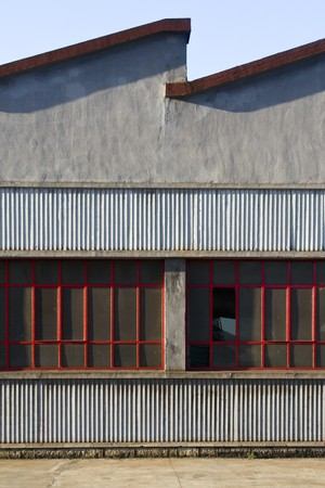 old industrial ship of cement and brick. The ceiling has the typical form of the old factories. The moldings of the large windows conserve the red color, although some of crystals appears broken Standard-Bild