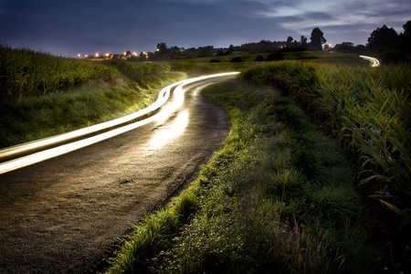 Sinuous rural road between meadows. The track of the lights of a car illuminates and draws the road . The night sky has a stormy aspect. To the bottom  a small village can be seen