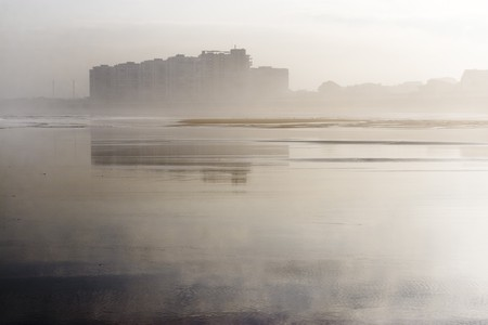Salinas, Asturias, north of Spain, between the fog and reflected in its beach in low tide Standard-Bild