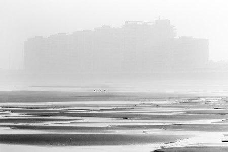 Beach in low tide with the silhouette of the city between the fog to the bottom