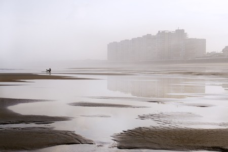Salinas, Asturias, north of Spain, between the fog and reflected in its beach in low tide. A small silhouette of a person putting on a few fins he stands out in the beach