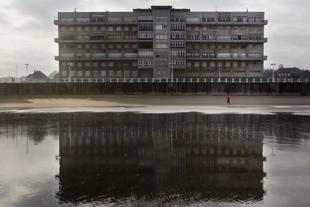 Geometric building next to the beach reflected in the low tide. The silhouette of a person is estimated runing along the this one