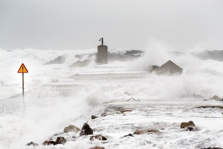 Storm in the sea with enormous waves invading the levee. A sign of danger notices of the risk