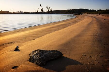 Beach in a ria with the derricks of an industrial wharf to the bottom contrasting with the tranquility of the sandbank