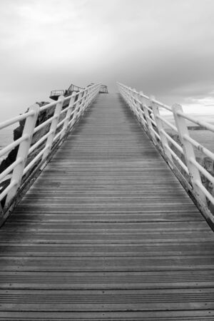 Gangplank of wood with metallic rails ascending towards a cloudy sky. Black & wite