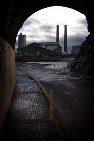 dismal: Sidewalk and causeway of a tunnel to the exit of which one sees an old factory. The atmosphere is dismal Stock Photo