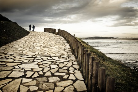 Couple and their dog in silhouette walking along a paved way to shore of the sea. The cloudy day and the hot dominant color they give a romantic aspect to the scene.