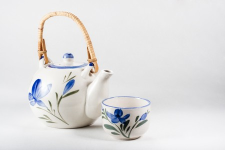 Tea-pot and cup of white porcelain refined decorated with floral motives in blue and green on white background