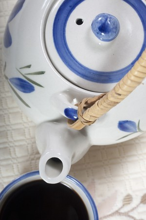 Cup of coffee and coffee pot of porcelain. Close- up capture and composition in diagonal on table cloth of linen