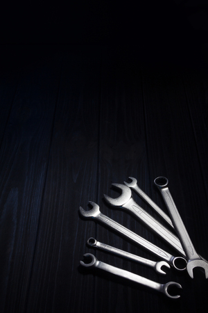 Several of wrenches on dark wooden board