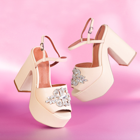 The pair of beautiful beige sexy high sandals on a pink background Stock Photo