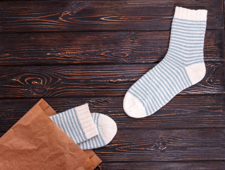 children s feet: Pair of womens striped socks whith a paper bag on a wooden background