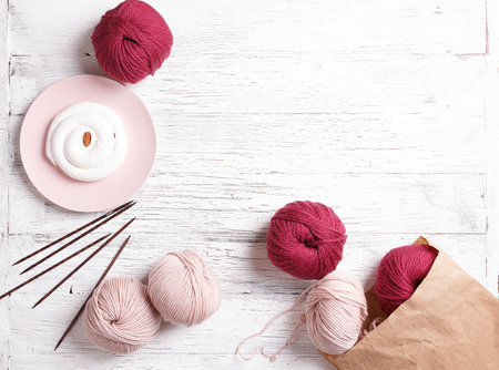 Knitting mood. Paper bag with yarn on a white wooden background. Pink plate whith a white cake. Spilled coils of yarn. Pink and dark red coil of yarn
