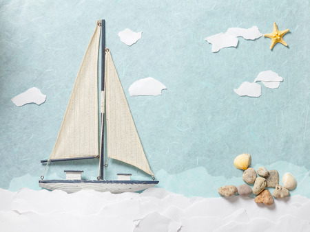 Wooden toy sailing boat on light blue paper background
