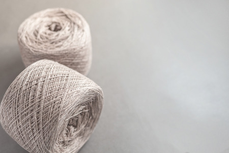 Two beige balls of threads wool yarn on gray paper