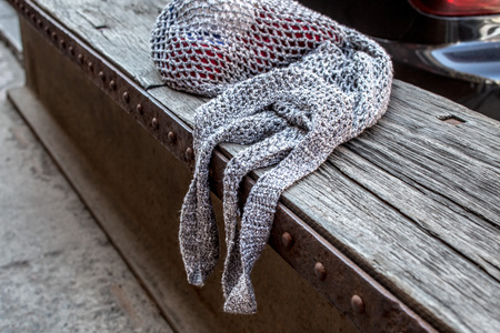 Gray string bag with red knitting clews on old wood texture background Reklamní fotografie