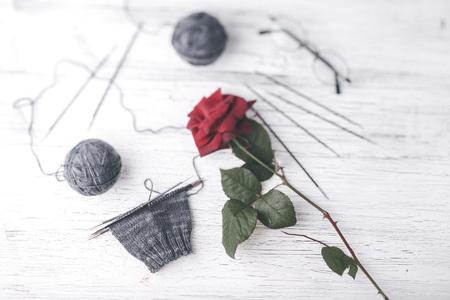 Gray knitting wool, knitting needles, glasses and single red rose Reklamní fotografie
