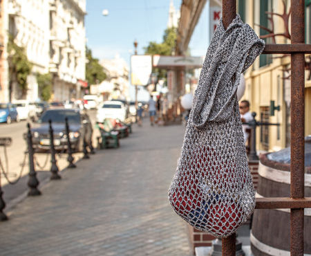 Gray string bag with red knitting yarn hanging on an old rusty metal fence, on the background of a sunny city street Stock Photo