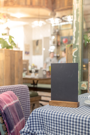 Blank chalkboard standing on table over blur cafe with bokeh background, space for text Reklamní fotografie