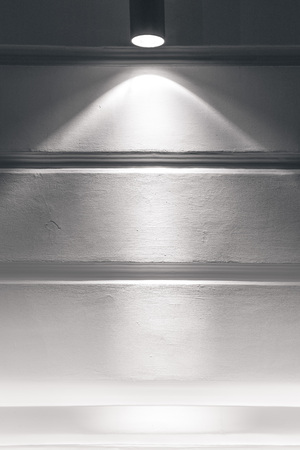 Gray plastered wall with a beam of light from the spotlight.