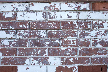 Old vintage brick wall with white paint that cracked with age