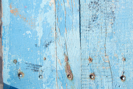 cracked horizontal wooden panel with peeling blue paint, textured surface background
