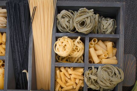 different stuffed pasta such as fusillini, sedani rigati, spaghetti, linguine, fettuccine in rustic old wooden box over on wooden flourish table. 版權商用圖片
