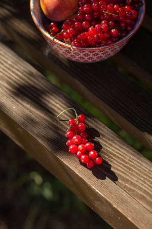 Peaches and currant berries on wooden swing in the rays of the summer slate. 版權商用圖片