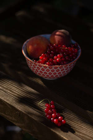Peaches and currant berries on wooden swing in the rays of the summer slate