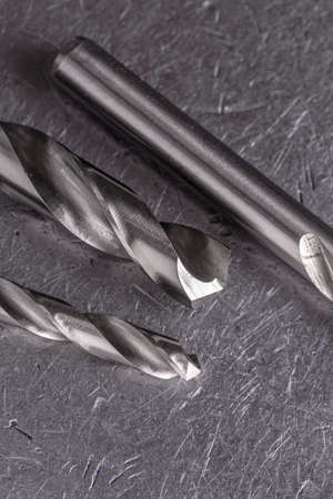 Concept metalworking. Metal drill bits on a metal old background with copy space.
