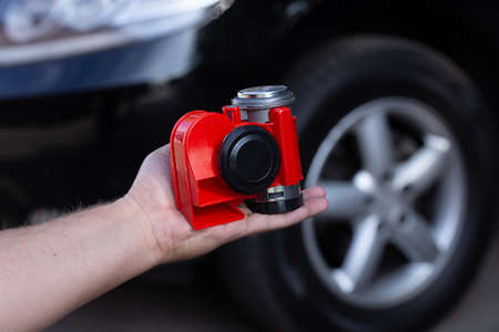 Red air horn for a car on mens hand before a modern black car. Electric Car air horn.