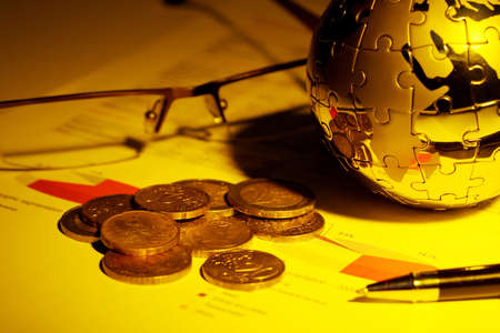 Globe puzzle and Euro coins on business document  Stock Photo