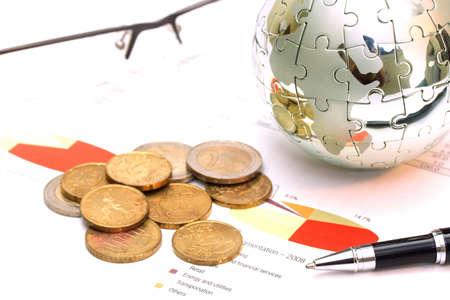 Globe puzzel en Euromunten op zakelijk document