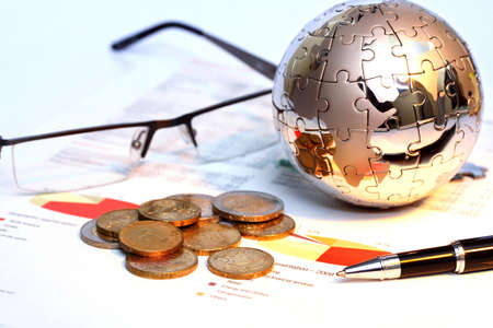 Globe puzzle and Euro coins on business document  photo