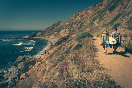 Young couple walking on a rugged trail with their surfboards in Palos Verdes Estates, California Stock Photo