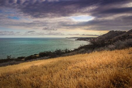 Dramatic clouds and coastline view of the Pacific Ocean from the Corral Canyon trail in Malibu, California