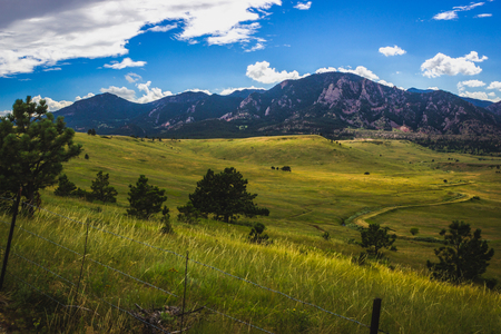 Beautiful Flatirons mountain and valley with winding road on a summer day with blue sky and clouds, Boulder, Colorado Archivio Fotografico