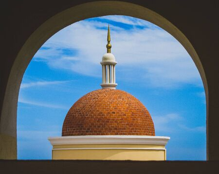 Orange brick dome rooftop of a building viewed through a round window in Cabo San Lucas, Mexico