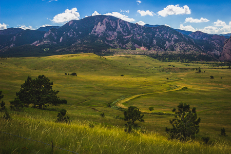 Flatirons mountain and valley with winding road on a summer day with blue sky and clouds, Boulder, Colorado