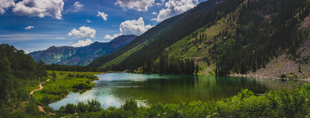Beautiful Maroon Lake and trail with blue sky and clouds in summer near Aspen, Colorado