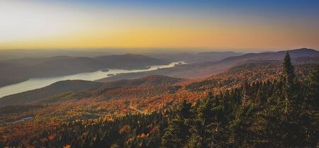 Aerial view of beautiful Lake Tremblant at sunset with colorful autumn foliage covering the mountains from the summit of Mont Tremblant, Quebec, Canada