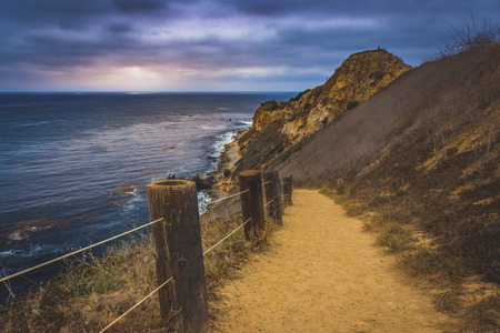 Coastal hiking trail cascading down the steep cliffs of Pelican Cove Park on a cloudy day with beams of sunlight poking through the clouds, Ranch Palos Verdes, California Stock Photo