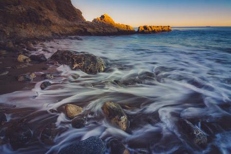 Close-up view of waves crashing onto shore and water trickling through rocks on Terranea Beach at sunset, Rancho Palos Verdes, California