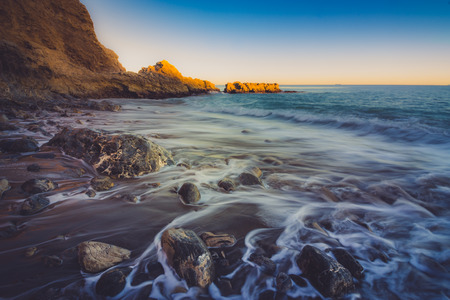 Close-up view of waves crashing onto shore and water trickling through rocks on Terranea Beach at sunset, Rancho Palos Verdes, California