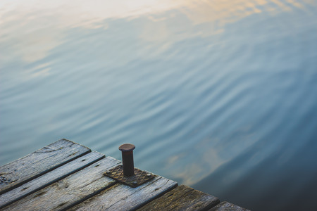 Close-up of a pier and water ripples on the waterfront of Sodermalm District at sunrise in autumn, Stockholm, Sweden
