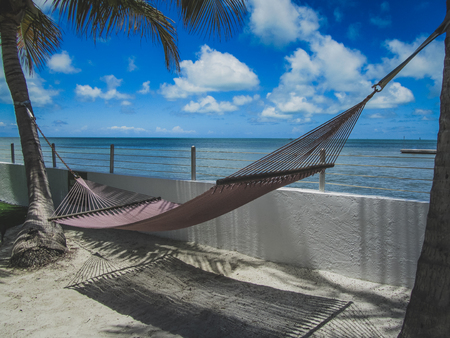Relaxing hammock tied to two palm trees with a stunning view of the ocean on a sunny day with blue sky and clouds, Key West, Florida Stock Photo