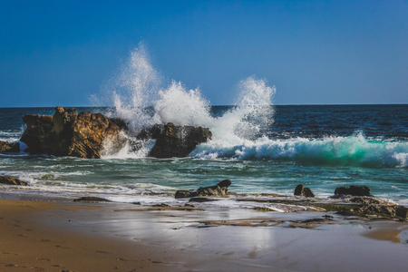 Beautiful beachfront view of waves crashing into rock formations on a sunny day with stunning blue water, Laguna Beach, California